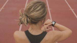 Frau misst ihren Puls beim Laufen