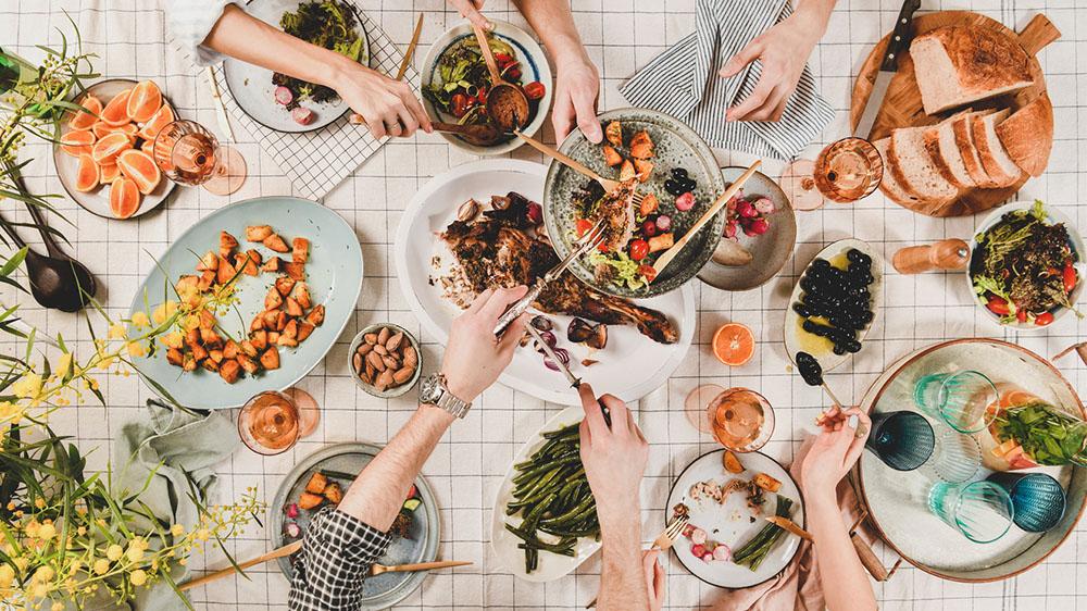 Leute sitzen an einem gedeckten Tisch mit vielen Gerichten