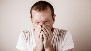 Hand vorm Mund beim Niesen