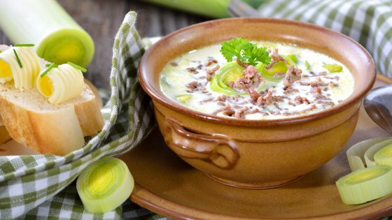 Creamy cheese and leek soup with minced meat, served with buttered baguette on a wooden table